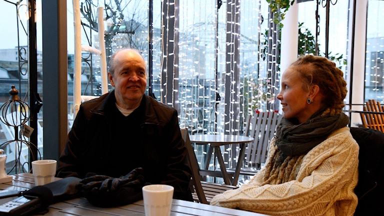 Lukupiiriläiset Keijo Knutas ja Hanna Hallakumpu istuvat kahvilla jouluvalojen loistaessa heidän takanaan.