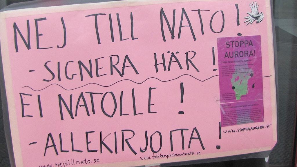 Lähikuva kyltistä, jossa lukee Ei Natolle! Allekirjoita!