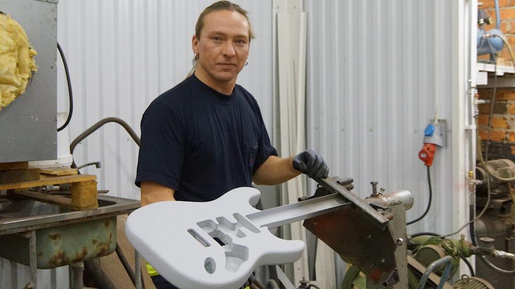 Artisten Nicke Sebbas, Piteå, i en bilverkstad där han är i färd med att måla om en elgitarr.