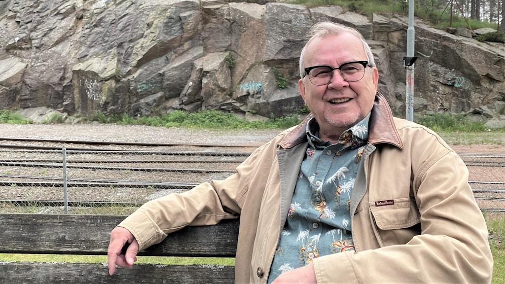 En man sitter på en parkbänk framför spårvagnsspår.