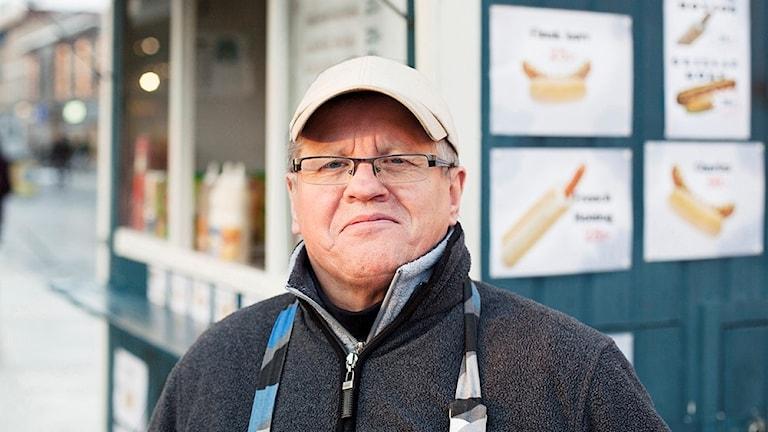 Helmer Holm står framför en blå korvvagn.