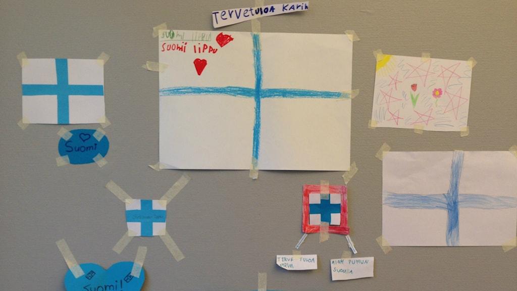 Ritade Finlands-flaggor, upphängda på en vägg i en skola.