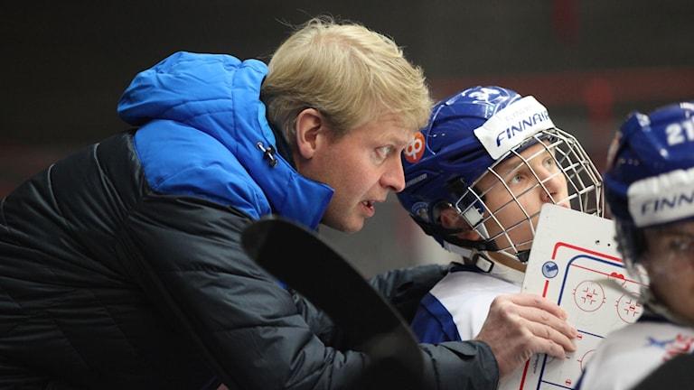 Kuvassa näkyy vaaleahiuksinen valmentaja joka nojaa nuoren maajoukkuepelaajan olan yli ja ohjeistaa tätä.