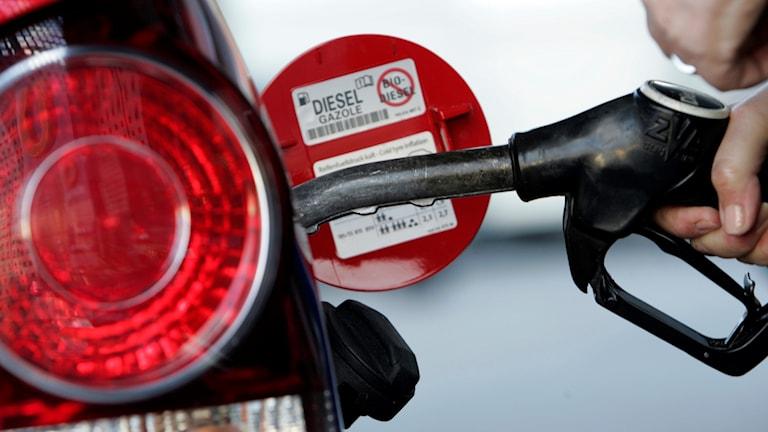 Kuvassa näkyy vasemalla isona auton punainen jarruvalo ja vasemalla auton tankki, johon tankataan dieseliä.