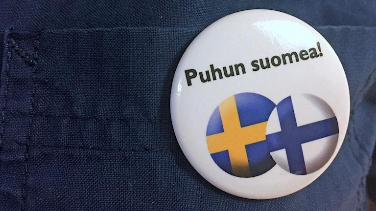 Valkoinen rintamerkki, jossa on pyöreät Suomen ja Ruotsin liput ja teksti Puhun suomea!