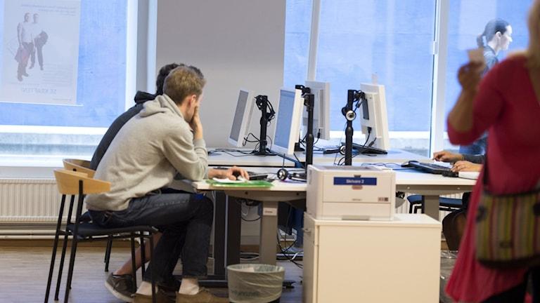 Nuoria istumassa tietokokoneilla työvoimatoimistossa.