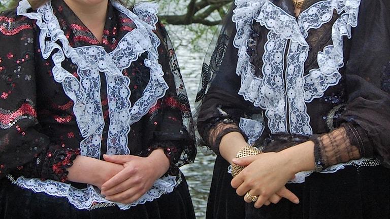 Kuvassa näkyy kahden perinteisiin suomalaisiin romaniasuihin pukeutuneen naisen kädet, vähän heidän tummia puseroitaan, joissa on valkoista pitsiä. Kuva: Riitta Niemi.