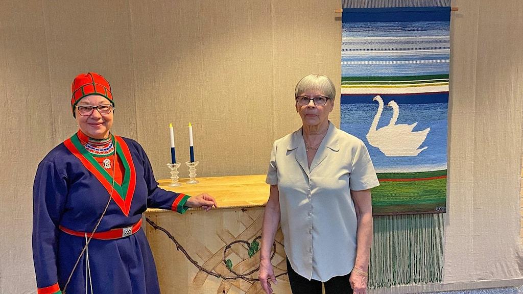 Pöydän äärellä saamelaispuvussa oleva nainen ja nainen harmaassa puserossa. taustalla raaniu jossa joutsenpari