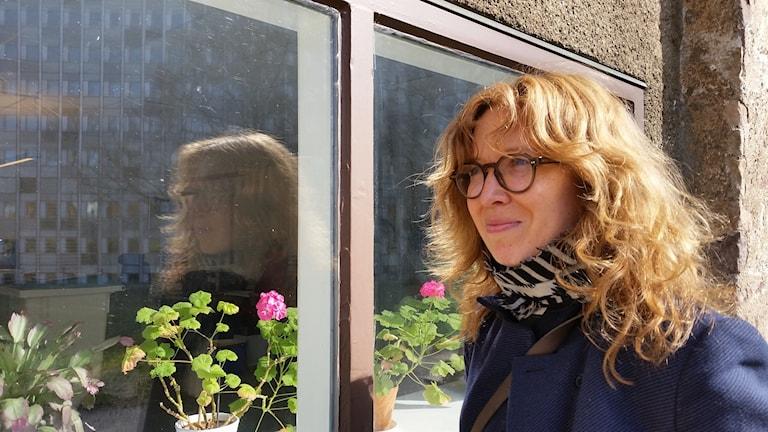Kuvassa Katja Seitajoki seisoo ulkona, auringonpaisteessa ikkunan vieressä, ikkunalaudalla näkyy kukkivia pergonioita ja ikkunalasissa heijastuu Katjan kuva ja harmaa rakennus. Kuva: Riitta Niemi/Sveriges Radio Sisuradio