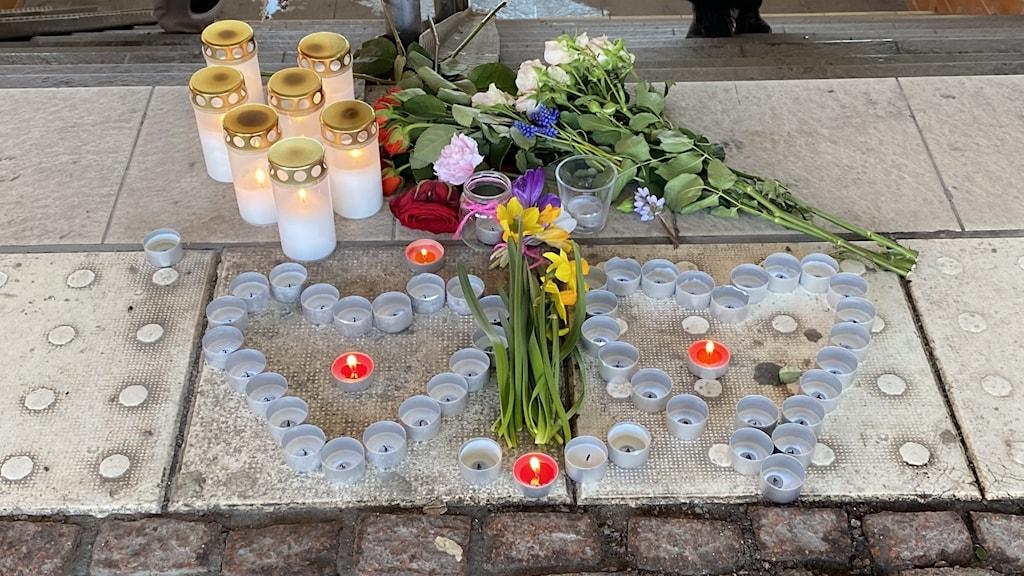 Kukkia ja kynttilöitä romaninaisen puukotuspaikalla.