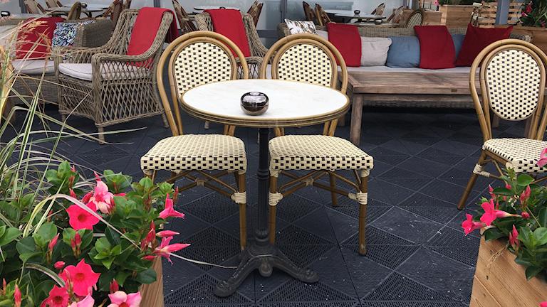 Kaksi tuolia ja pöytä jossa tuhkakuppi terassilla. Tiukennetun tupakointikiellon mukaan, terassin omistajan pitää tiedottaa uusista säännöistä, mutta tarkkoja sääntöjä ei ole.