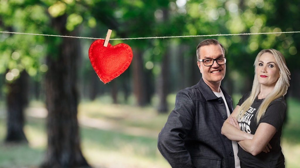 Programledarna står framför en skog och en lina där det hänger ett rött tyghjärta.