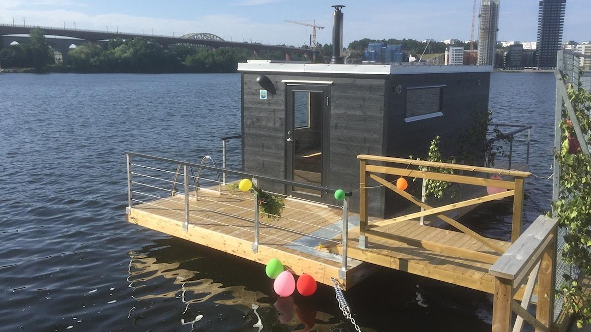 Kelluva mustamaalinen sauna, jonksa lauturissa kiinni muutamia ilmapalloja. Kuva: Timo Laine/Sveriges Radio Sisuradio