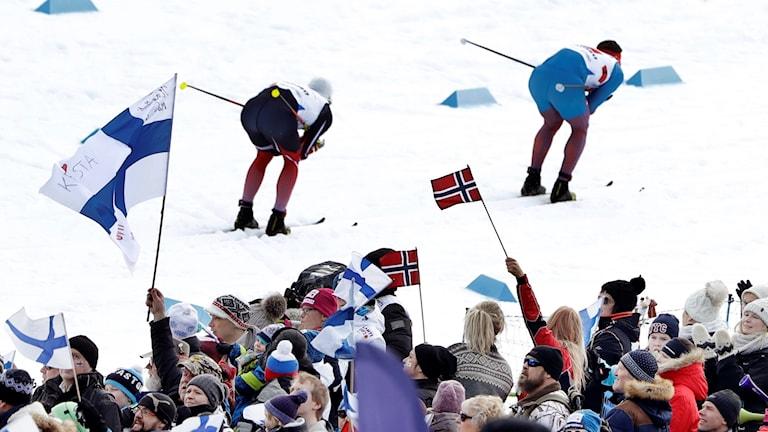 Kaksi hiihtäjää ja yleisö Lahden MM-kisoissa. Yleisössä liehuvat Suomen ja Norjan liput.