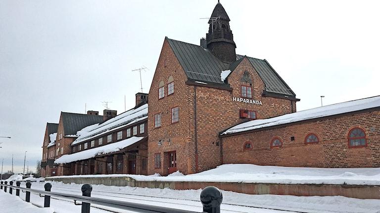 Punatiilinen rautatieasemarakennus lumisessa maisemassa.