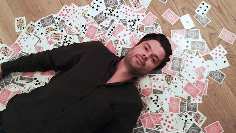 En man ligger på golvet på kortlek