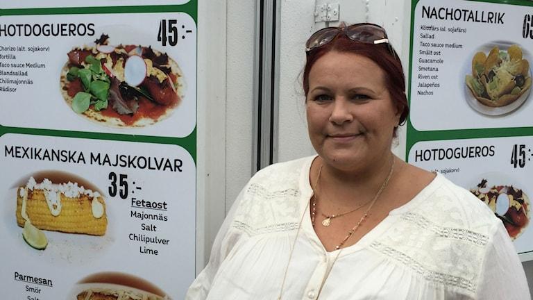 Tenja Karlsson ruokavaununsa edustalla, taustalla kuvia eri meksikolaisista ruokalajeista, esim. nachotallrik
