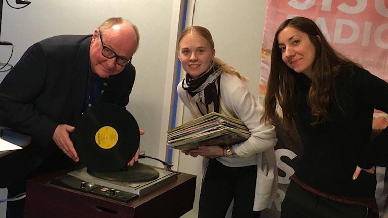 Jorma Ikäheimo, Matilda Peltonen ja Elvira Björnfot levysoittimen äärellä.
