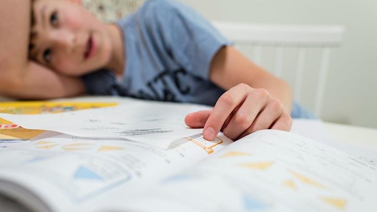 Pojke sitter vid bord med läroböcker.