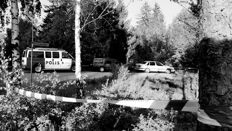 Kuva on Hovsjön surmapaikalta, mustavaloisessa kuvassa näkyy poliisin sulkunauna puitten välissa ja taaempana poliisiauto.