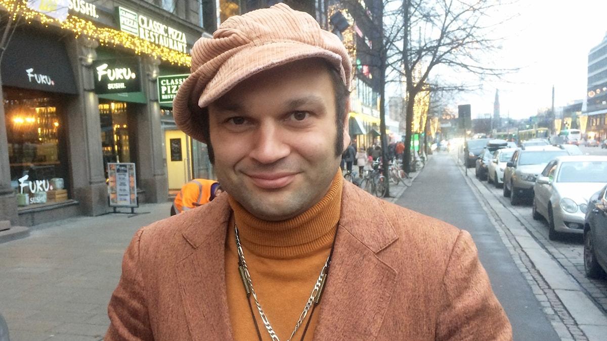 Dimitri Keiski katsoo hymyillen kameraan, hänellä on lakki päässä.