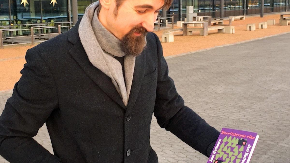 En man står utanför en glasbyggnad med en bok i hand