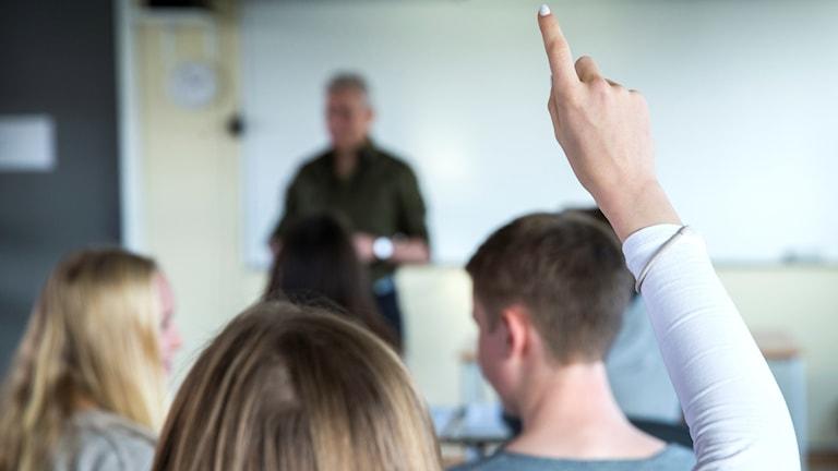 En klass med läraren i bakgrunden och en elev som sträcker upp handen.