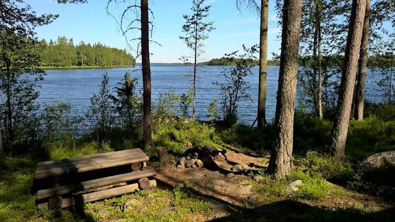 Mökkiranta Suomessa, pihassa puinen pöytä ja penkit, sekä kivistä tehty grillipaikka, järvi kimaltelee sinisenä. Kuva: Martti Paananen.
