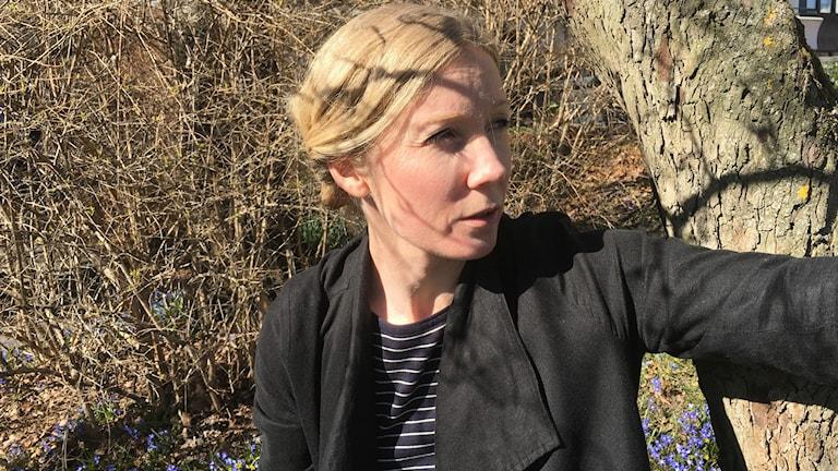 Minna Heimo osoittaa oikealle, takana oikealla puunrunko, vasemmalla puskaa ja maassa pilkottaa sinisiä kevätkukkia. Kuva: Riitta Niemi/ Sveriges Radio Sisuradio