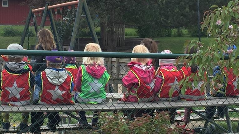 Förskolebarn sitter på en bänk