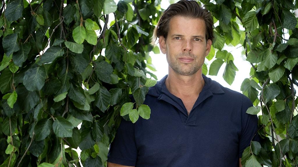 Alex Schulman tittar in i kameran med en samlad blick. Han står under ett träd och omgärdas av lummiga grenar som hänger ner.