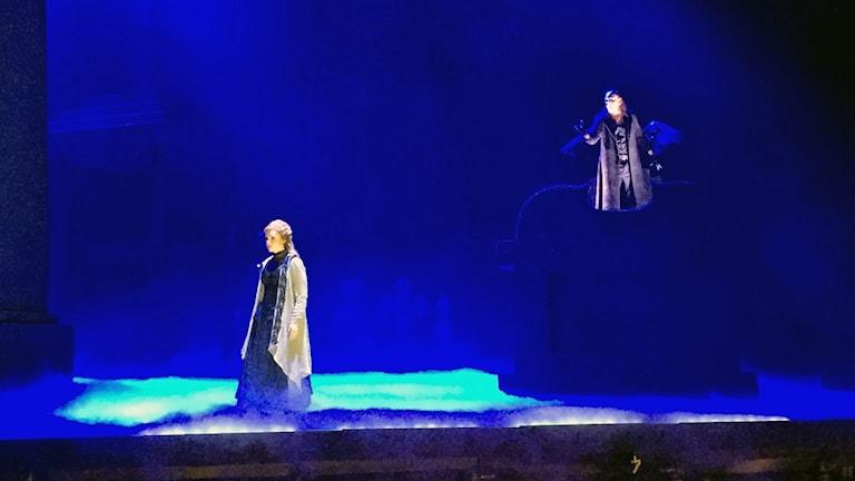 En kvinnlig och en manlig skådespelare på en blå scen