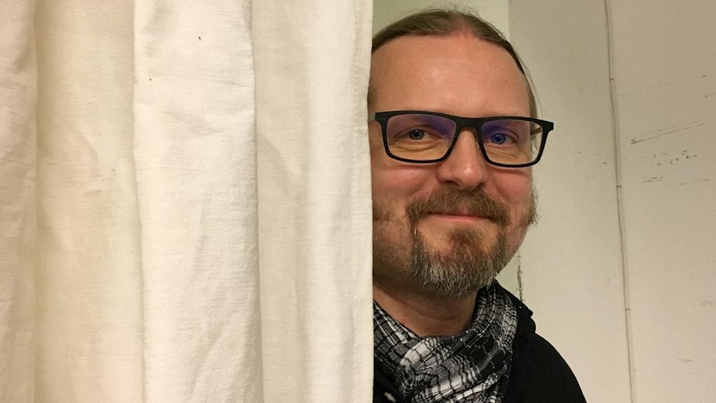 Hymyilevä Marko Hautala katsoo kameraan kohti  valkoisen verhon takaa
