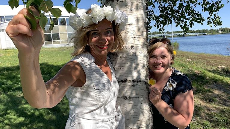 Kaksi naista seisomassa valkean koivurungon molemmin puolin joen rannalla kesällä auringonpaisteessa. Toisella seppele päässä ja toisella kukkia kädessä. Molemmilla leningit yllään ja tummanruskeat hiukset.