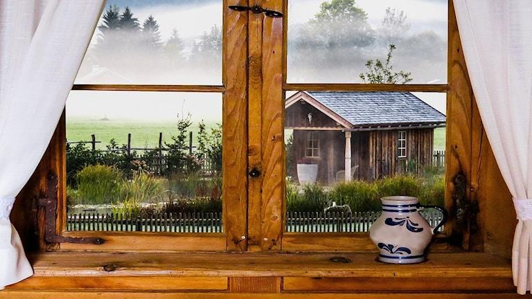 Mökin ikkunasta näkyvä maisema, pihalla sumua ja pieni pihamökki