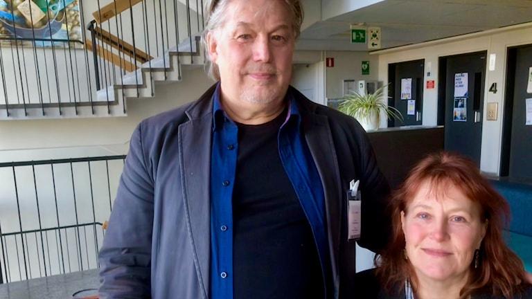Harmaatakkinen Esa Rautiainen seisoo ja punahiuksinen Elina Söderström istuu katsoen kameraan rappukäytävässä. Kuva: Timo Laine/SR Sisuradio