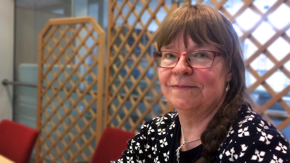 En kvinna med glasögon tittar rakt i i kameran.