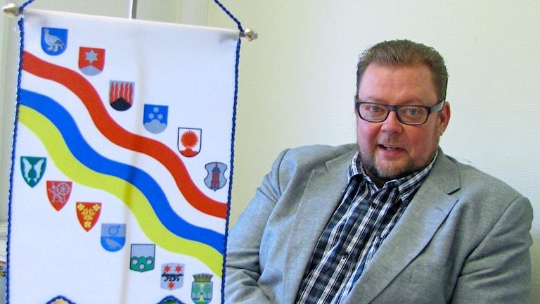 Silmälasipäinen mies lähikuvassa istumassa puvuntakki päällä Tornionlaakson neuvoston viiri etualalla.