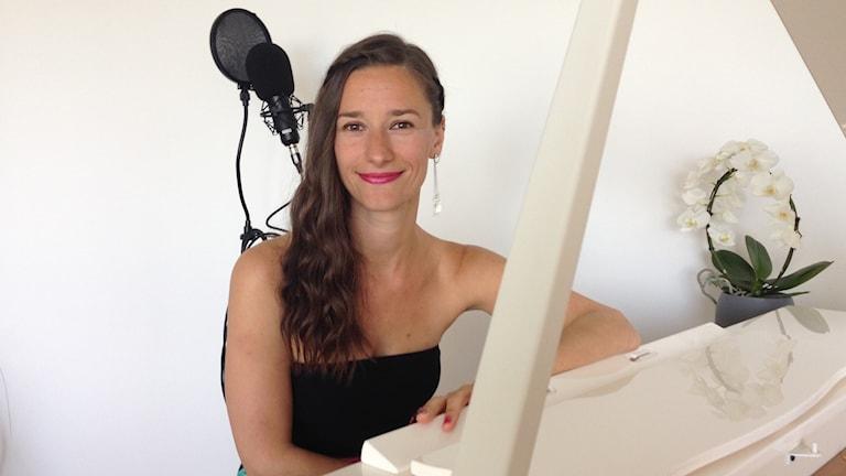 Laulaja Lucie Niemelä istuu pianonsa ääressä.