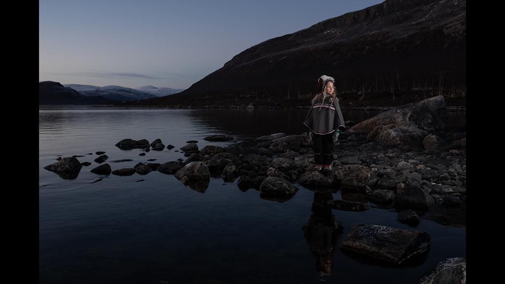 Tyttö seisoo veden äärellä ja katsoo kaukaisuuteen.