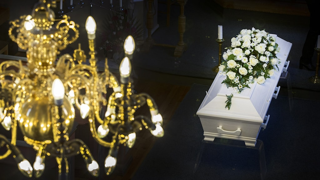 Kultainen kirkon kattokruunu ylhäällä vasemmalla etualalla ja oikealla alhaalla valkoinen arkku, jonka päällä valkoisia kukkia.