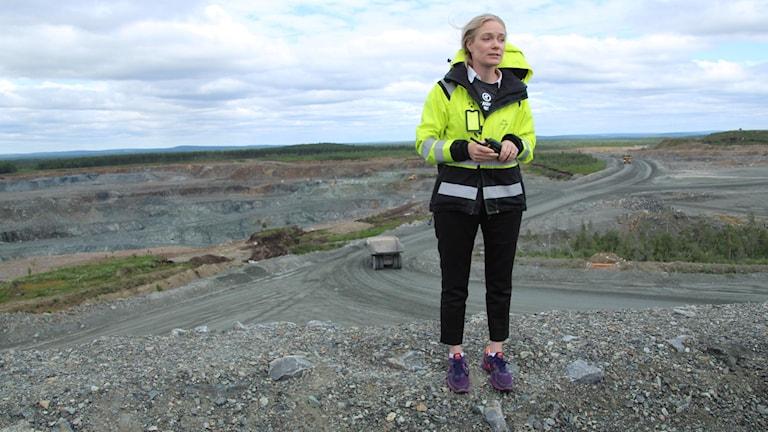 Keski-ikäinen, vaaleahiuksinen nainen seisoo kaivosalueen laidalla keltaisessa turvatakissa.