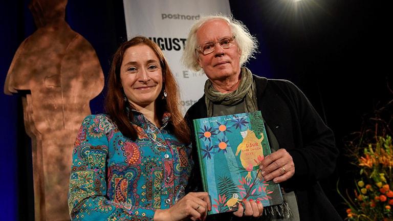 Kuvittaja Linda Bondestam ja kirjailija Ulf Stark pitävät käsissään tekemäänsä lastenrunokirjaa.