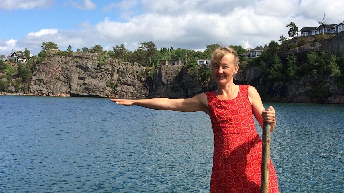 Tara Salokorpi punaisessa kesämekossaan laiturilla meren rannalla