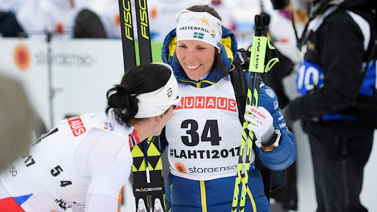 Kuvassa kuksiaan ja sauvojaan piteleva, naurava Charlotte Kalla onnittelee juuru maaliin tullut Marit Björgenia. Kuva: Anders Wiklund
