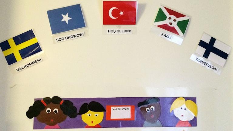 Seinällä viiden maan liput joiden alla lukee tervetuloa eri kielillä.