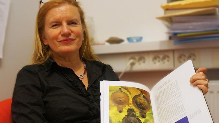 Arja Karivieri näyttää kirjasta antiikin aikaisia lamppuja