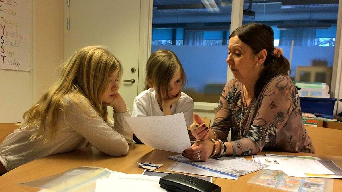 Opettaja Maarit Virkkunen ja tytöt Myra Bell ja Selma suomen tunnilla Ölmstadin koulussa.