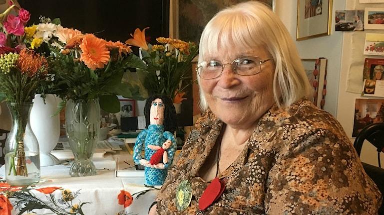 Thelma Aulio Paananen istuu pöydän ääressä, pöydällä on paljon kukkia ja yksi virkattu nukke. Kuva: Riitta Niemi/ Sveriges Radio Sisuradio