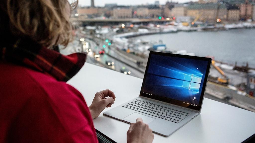 Kuvassa näkyy nainen katsomassa kannettavan tietokoneen ruutua, korkealla esim. kahvilassa. Ikkunasta näköala Tukholman keskustaan.